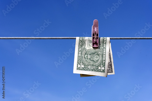 Fototapeta Money laundering of a one US Dollar bill note from the USA on a washing line with blue sky for AML Anti laundering finance business crime ideas obraz