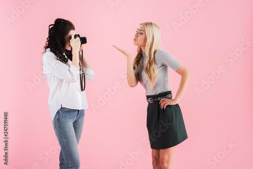 Fotografia  Brunette women taking photo while blonde girl sending air kiss isolated on pink