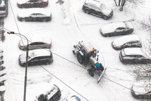 Road Cleaning In Parking Area With Tractor In Snow