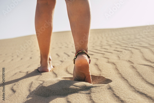 Woman walking barefoot on desert dunes leaving footprints in the sand Canvas Print