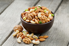 Wooden Bowl With Mixed Nuts On A Wooden Gray Background. Walnut, Pistachios, Almonds, Hazelnuts And Cashews, Walnut.