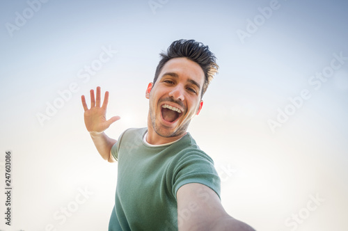 Fotografía  Man taking a selfie on a blue sky background