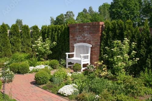 Zdjęcie XXL Biała ozdobna ławka przy ceglanym murze otoczona pięknym romantycznym ogrodem