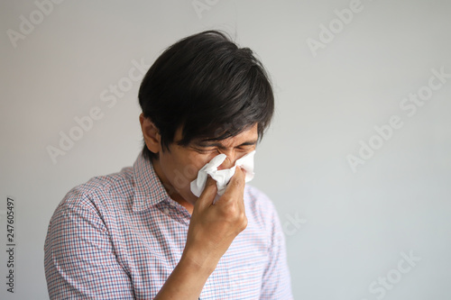 Photo  Asian man wipe his nose with tissue looks