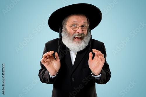 Fototapeta Portrait of old senior orthodox Hasdim Jewish man with wooden Grager Ratchet at Jewish festival of Purim at studio. The purim, jewish, festival, holiday, celebration, judaism, pastry, tradition obraz