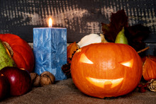 Halloween Concept. Carved Pumpkin With Candle On Jute Bag Surrounded By Autumn Fruit With Background From Old Planks.
