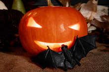 Halloween Concept. Carved Shining Pumpkin With A Bat On A Jute Bag With A Background Of Old Planks.