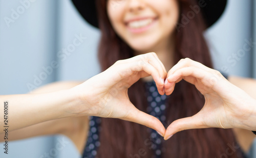 Fotografie, Obraz Closeup shot of cheerful girl with long hair making heart shape with her fingers