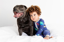 Young Boy Leaning Against Dog On Bed