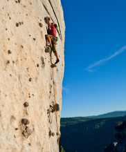 Low-angle View Of Rock Climber Climbing On Vertical Mountain Side.