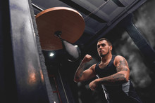 Born To Win. Muscular Tattooed Athlete In Sports Clothing Training Hard On Punching Speed Bag To Become A Champion, Boxing Gym Interior