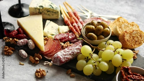 Cold snacks board with meats, grapes, wine, various kinds of cheese Canvas Print