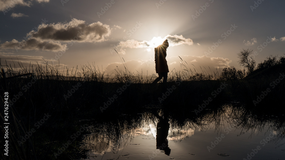 Fototapeta silhouette of a lonely woman walking at a pond in the evening of an cold sunny winter day