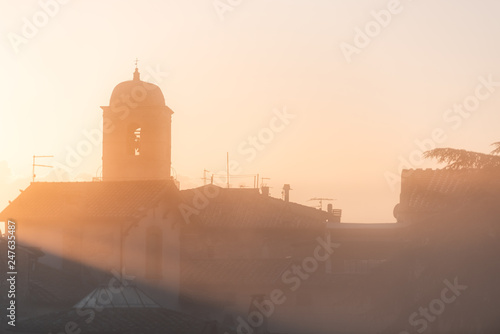 Chiusi mist fog sunrise of Cathedral Church bell tower in Umbria, Italy near tuscany with warm sepia soft orange golden yellow brown vintage color cityscape