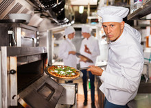 Confident Chef Getting Pizza Out Of Oven