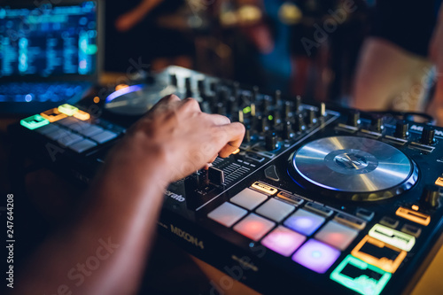 DJ plays live set and mixing music on turntable console at stage in the night club. Disc Jokey Hands on a sound mixer station at club party. DJ mixer controller panel for playing music and partying. - 247644208