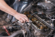 Auto mechanic working on car engine at repair service. Close up view .