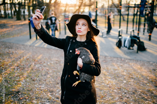 Photo Beautiful young attractive brunette model girl with long hair in black coat and elegant hat making selfie with chicken with a view at training ground with sunset light on background in spring