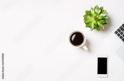 Laptop computer with plant in a pot, cup of coffee and modern mobile phone on white background. Conceptual workspace or business concept. Free space for your text - 247649010
