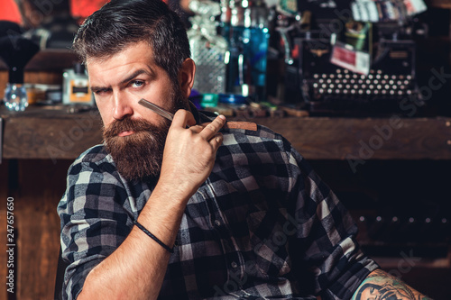 Bearded man, long beard, brutal, caucasian hipster with moustache. Mens haircut in barber shop. Straight razors, barbershop, beard, blade.