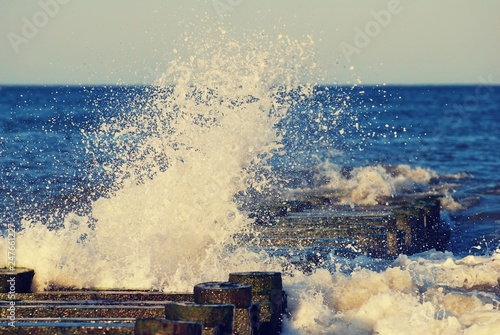 Poster Bordeaux Close up on ocean wave hitting wood pier
