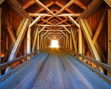 Inside Lowe's Covered Bridge In Maine, With Light At The End.