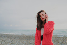 Sad Brunette Girl In Red Cardigan Alone On Empty Seashore In Windy Weather