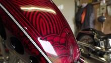 Handheld Moving Shot Of Custom Motorbike Red Design Petrol Tank In Workshop With Harley Davidson In Background.