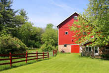 Beautiful Spring Landscape With Red Barn. Scenic View With Old Style Red Barn Between Fresh Green Color Trees. Green Grass Field With Daffodils In A Foreground. Rural Life And Farming Background.