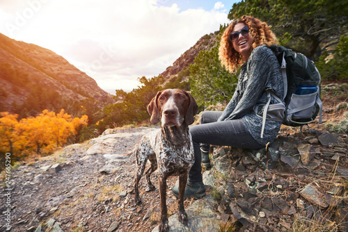 фотография a young woman and her dog hiking to the top of a mountain
