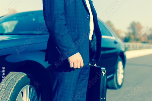 Fotomural .a businessman standing near in front of.luxury car holding brief case or diplom
