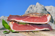canvas print picture - Südtiroler Speck auf einem Holztisch vor Bergen in den Alpen – Typical South Tyrolean bacon divided into two halfes lying on a rustic table in front of mountains of the alps