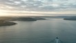 AERIAL: From Padstow Bay out towards Daymer Bay at sunrise with a boat heading to padstow harbour, Cornwall, UK