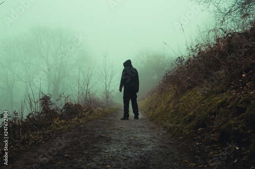 Fotografía  An eerie hooded figure standing on a path on a spooky foggy winters day in the countryside