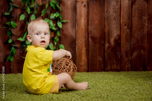 Photo  Portrait of a cute little european girl sitting in the yellow shirt on a green c