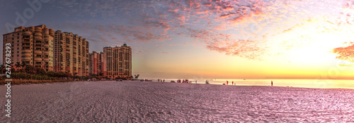 Tuinposter Cappuccino Pink and gold sunset sky over South Marco Island Beach