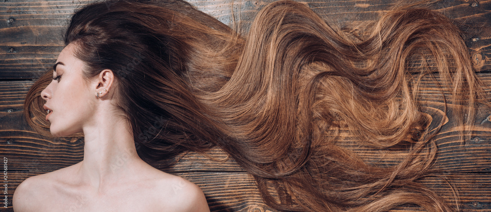 Fototapeta Woman with beautiful long hair on wooden background. Long hair. Trendy haircuts. Beauty hair Salon.