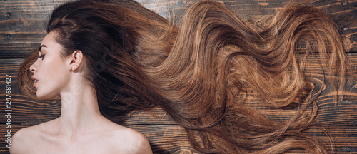 Foto auf Leinwand Friseur Woman with beautiful long hair on wooden background. Long hair. Trendy haircuts. Beauty hair Salon.