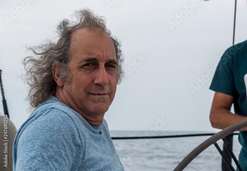 Fotografie, Obraz  Closeup of an older man sitting on a sailboat smiling