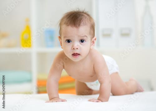 Photo  pretty crawling caucasian baby boy werared diaper indoor