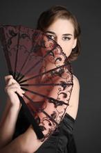 Stylish Girl In A Black Dress With A Fan.