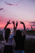 A hands in the form of love word. Sign of valentine day at sunset with landscape view of a local beach.
