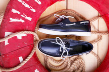 Blue Boat Shoes On Wooden Background Near Red Lifebuoy And Rope.
