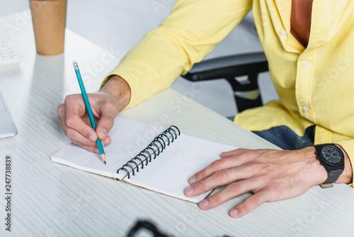 Staande foto Hoogte schaal Cropped view of man writing in notebook at desk