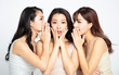 Three asian women telling whispering and secret gossip