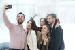 creative business group takes selfies in a modern office