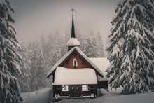 A Beautiful Small Wooden Chapel Standing In The Frozen Winter Forest In The Mythen Region, Switzerland