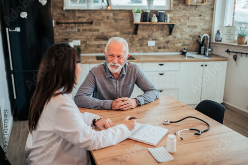 Obraz na plátně Female doctor talking to a senior patient during home visit.