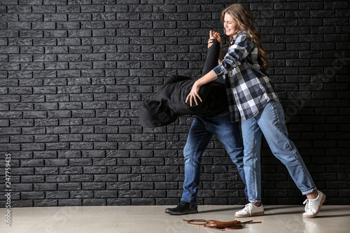 Fotografia  Young woman defending herself from attack by thief near dark brick wall