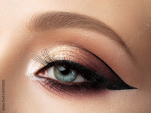 Obraz Close up of beautiful woman eye with multicolored fashion makeup and modern eyeliner wing. Studio shot - fototapety do salonu